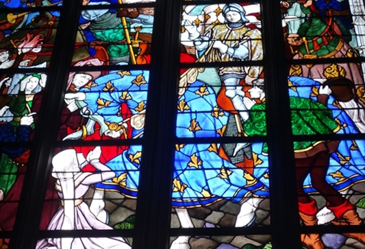 Photo of a stained glass by Jacques Galland and Esprit Gibelin depicting Joan of Arc live to illustrate  the Orléans Joan of Arc Walking Tour in the Loire Valley, France.